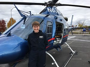 Flight nurse standing in front of helicopter.